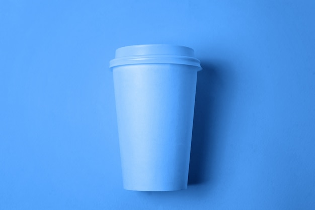 Simply flat lay design paper coffee cup colored in trendy color of year 2020 classic blue background. bright macro using color . top view copyspace
