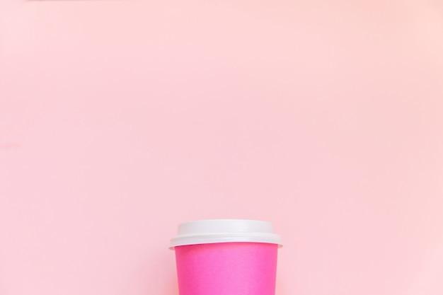 ピンクのパステルカラーの背景にシンプルなフラットレイデザインのピンクの紙のコーヒーカップ