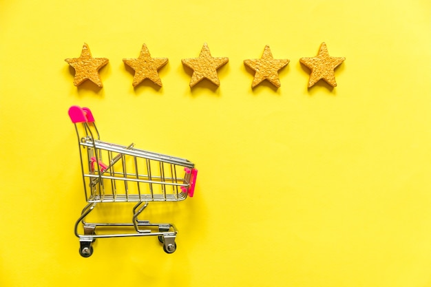 ホイールと黄色で分離された5つの金の星の評価で買い物をするための単純なフラットレイデザインの小さなスーパーマーケットの食料品プッシュカート