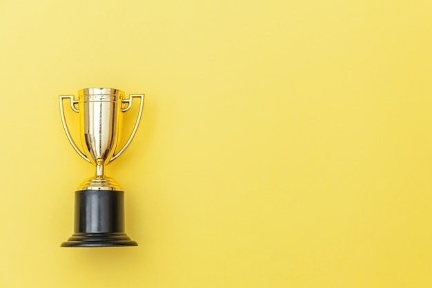 Simply flat lay design winner or champion gold trophy cup isolated on yellow colorful