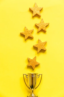 Simply flat lay design winner or champion gold trophy cup and stars rating isolated on yellow