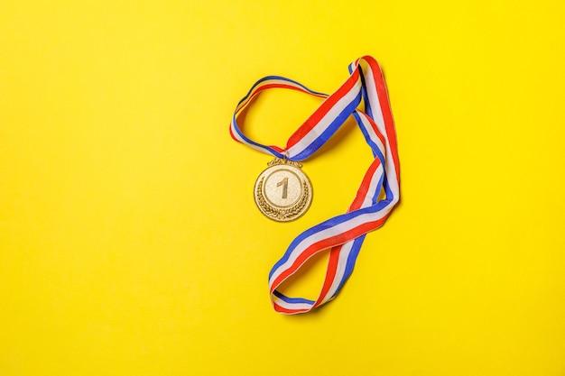 노란색 화려한 배경에서 분리된 단순히 평평한 평신도 디자인 우승자 또는 챔피언 금 트로피 메달. 경쟁의 승리 1 위. 승리 또는 성공 개념입니다. 상위 뷰 복사 공간입니다.