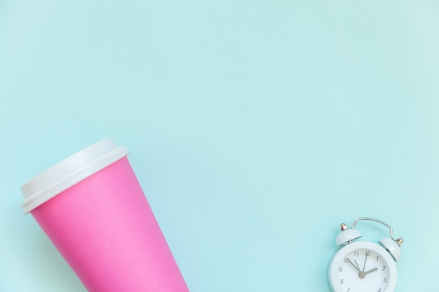 Просто плоская розовая бумажная кофейная чашка и будильник, изолированные на синем пастельном фоне