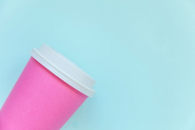 青いパステルカラーの背景に単に平らなピンクの紙のコーヒーカップを置く