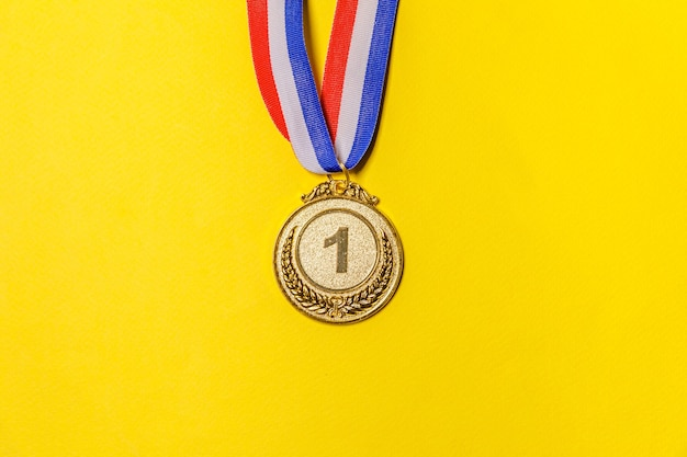 Simply flat lay winner or champion gold trophy medal isolated on yellow colorful background.