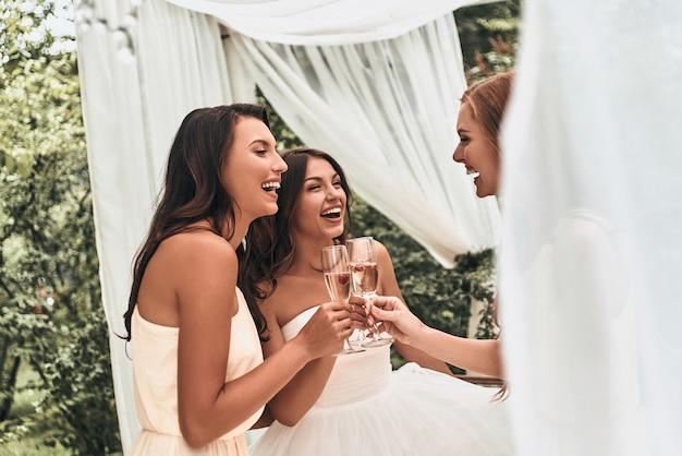 Просто доволен. привлекательная молодая невеста жарит шампанское и разговаривает со своими красивыми подружками невесты, стоя на открытом воздухе вместе
