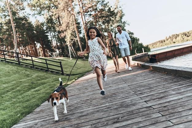 단순히 행복합니다. 그녀의 부모가 뒤에 걷는 동안 강아지와 함께 달리고 웃는 귀여운 소녀의 전체 길이