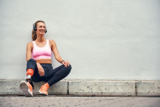 Просто счастливая молодая улыбающаяся женщина с протезом ноги в спортивной одежде и наушниках слушает