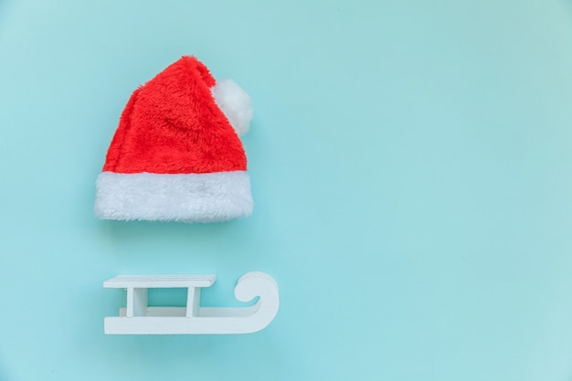 Simply minimal composition christmas santa claus hat sled isolated on blue background