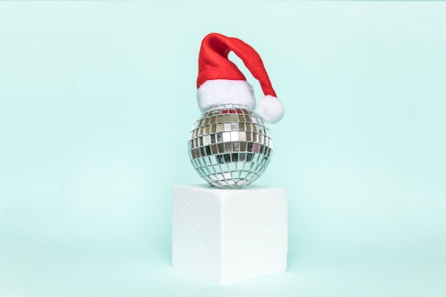 Simply minimal composition disco ball in santa hat and cube shapes geometric form podium isolated blue pastel background. christmas new year december time for celebration concept. mockup, copy space