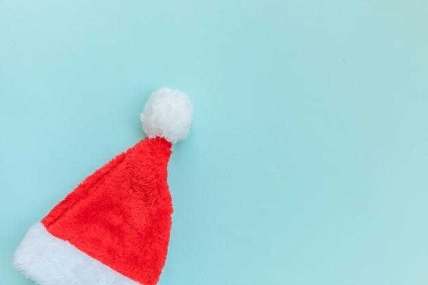 ブルーパステル背景に分離されたシンプルなミニマルなデザインのクリスマスサンタクロースの帽子