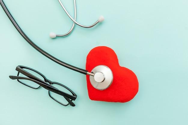 단순히 최소한의 디자인 의학 장비 청진기 안경 및 유행 파스텔 파란색 배경에 고립 된 붉은 심장