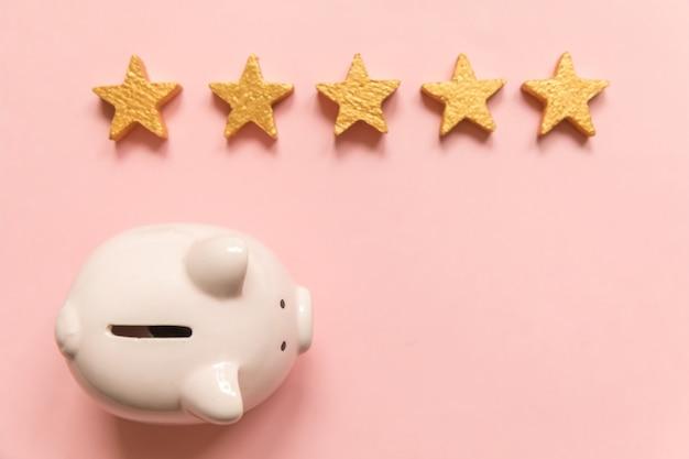 단순히 최소한의 디자인 돼지 저금통 분홍색 배경에 고립 된 5 개의 금색 별