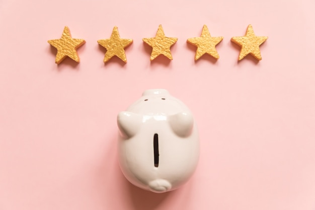 Simply minimal design piggy bank 5 gold stars isolated on pink background