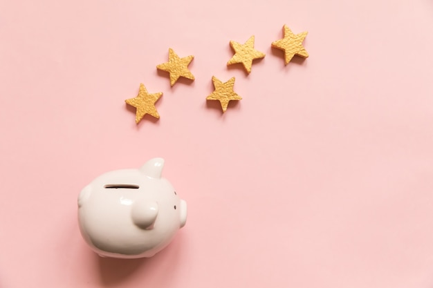 Simply minimal design piggy bank five gold stars isolated on pink