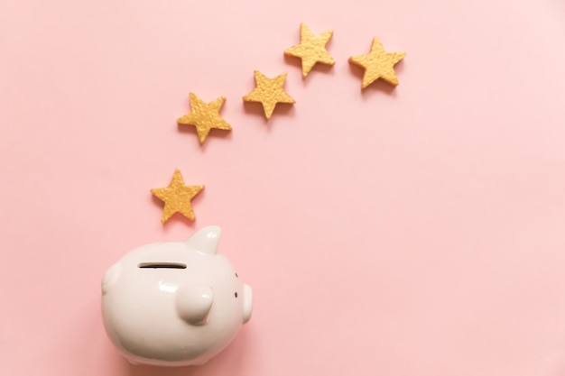 Simply minimal design piggy bank gold stars isolated on pink