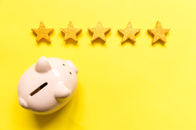 Simply minimal design piggy bank gold stars isolated on yellow