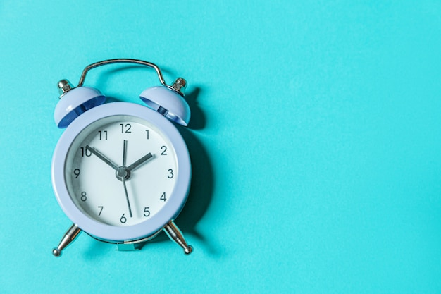 Simply minimal design ringing twin bell vintage classic alarm clock isolated on blue pastel background