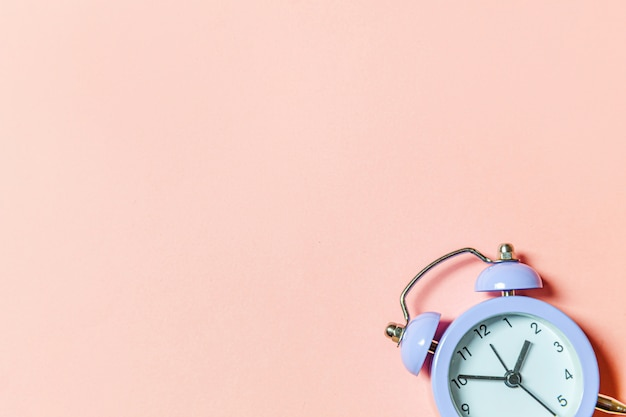 Simply minimal design ringing twin bell vintage classic alarm clock isolated on pink pastel background
