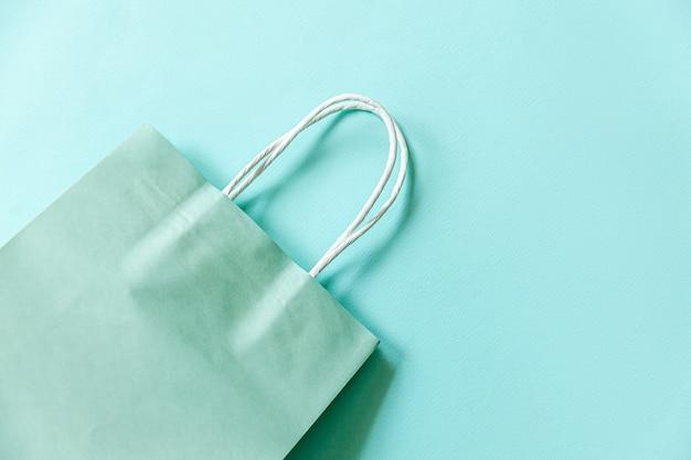 ブルーパステルの背景に分離されたシンプルなミニマルなデザインのショッピングバッグ