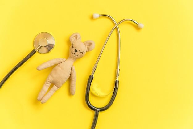 黄色に分離されたシンプルなデザインのおもちゃのクマと医療機器聴診器