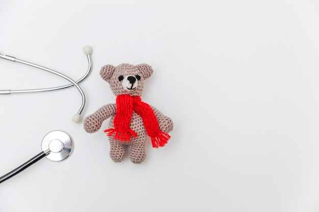 Simply minimal design toy bear and medicine equipment stethoscope isolated on white surface. health care children doctor concept. pediatrician symbol. flat lay, top view copy space