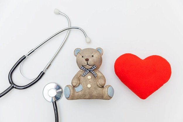 Просто минималистичный дизайн игрушечный медведь с красным сердцем и стетоскоп медицинского оборудования, изолированные на белом фоне