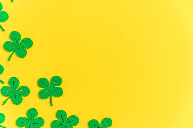 녹색 토끼풀 클로버 잎으로 단순히 최소한의 디자인은 노란색 배경에 고립