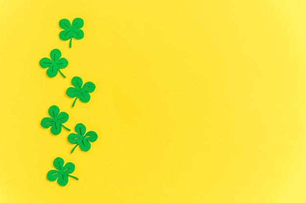 노란색 바탕에 녹색 토끼풀이있는 단순한 최소한의 디자인