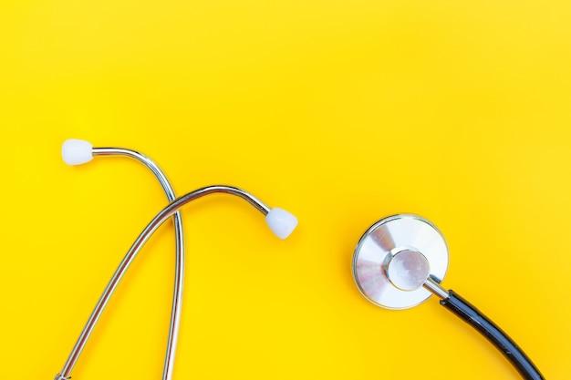 トレンディな黄色で分離された医療機器聴診器または電話内視鏡を使用したシンプルな最小限のデザイン
