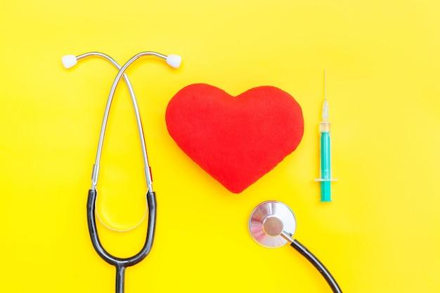 의학 장비 청진기 주사기와 트렌디 한 노란색 배경에 고립 된 붉은 마음을 가진 단순히 최소한의 디자인