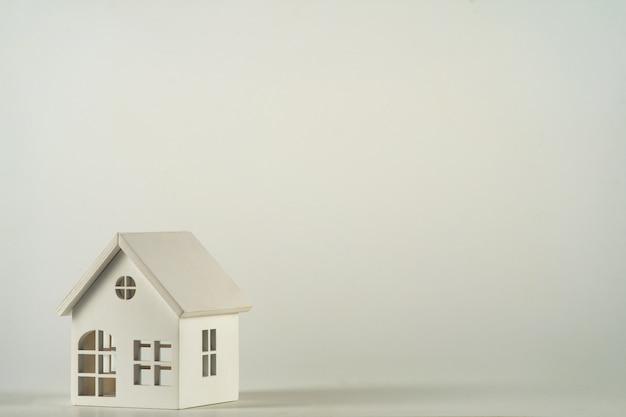 흰색 배경에 격리된 미니어처 장난감 집이 있는 최소한의 디자인입니다. 모기지 재산 보험 꿈의 집 개념