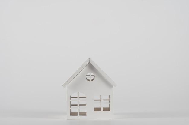 흰색 배경에 격리된 미니어처 장난감 집이 있는 최소한의 디자인입니다.