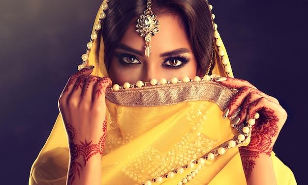 サリーベールの上の美しい黒い目の誠実で鋭い外観高級な黄色のサリー衣装に身を包んだ黒い髪のインドの若い女性インドの美しさ