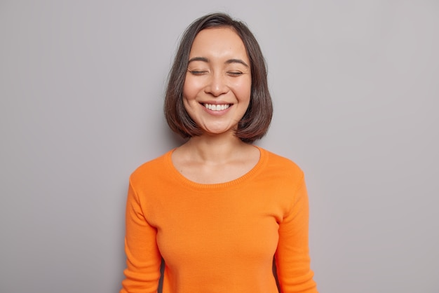Искренняя красивая азиатка рада слышать трогательные слова с закрытыми глазами, нежно улыбается, имеет натуральные темные волосы, здоровая кожа, одетая в повседневный оранжевый джемпер, позирует у серой стены