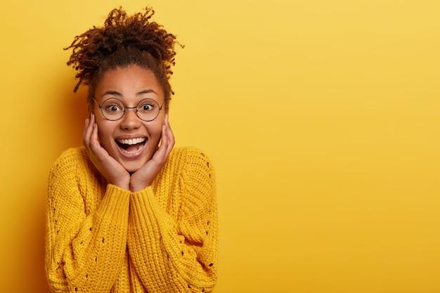La bella femmina sincera ride sopra lo scherzo divertente, sorride alla macchina fotografica con espressione spensierata