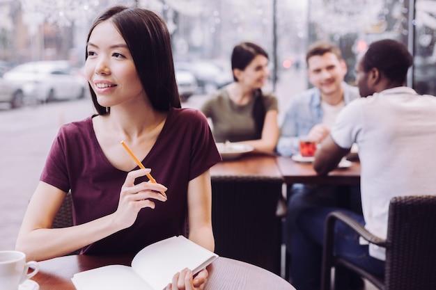 Искренняя красивая студентка смотрит в сторону и держит карандаш при планировании выполнения задания