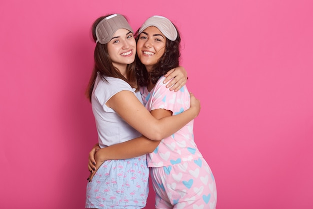Sincere beautiful friends posing isolated over pink, hugging each other, smiling