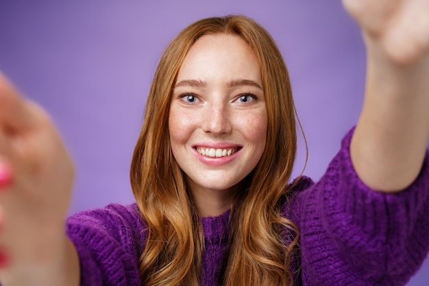 Sincere bright and cheerful ginger girl in purple sweater reaching camera with hands and smiling broadly with friendly optimistic gaze, taking selfie or wanting hold something over violet wall.