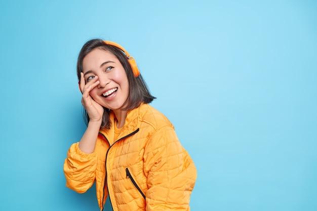 성실한 평온한 아시아 여자는 거리를 걷는 동안 기꺼이 얼굴을 손바닥으로 미소 짓습니다. 무선 헤드폰을 통해 음악을 듣고 빈 복사본 공간이있는 파란색 벽에 행복한 분위기 모델이 있습니다. 프리미엄 사진
