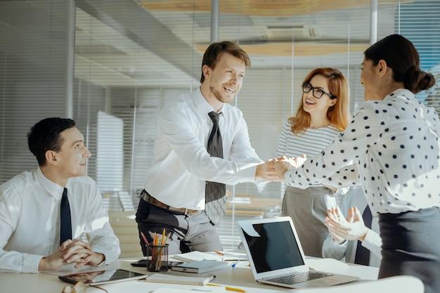 Искренние поздравления. очаровательный приятный босс пожимает руку своей коллеге, поздравляя ее с повышением по службе, в то время как другие коллеги аплодируют