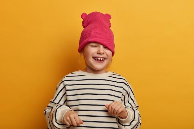 誠実な感情的な子供は、新しい帽子で遊んで、縞模様のジャンパーを着て、笑って何かを応援し、面白い楽しい表情、遊び心のある気分、夢中になる、鮮やかな黄色の壁に隔離されています