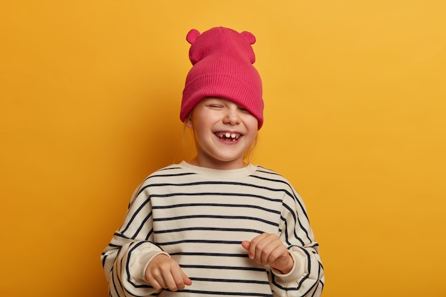 Sincere emotional child plays with new hat, dressed in striped jumper, laughs and cheers something, has funny joyful expression, playful mood, going crazy, isolated on vibrant yellow wall
