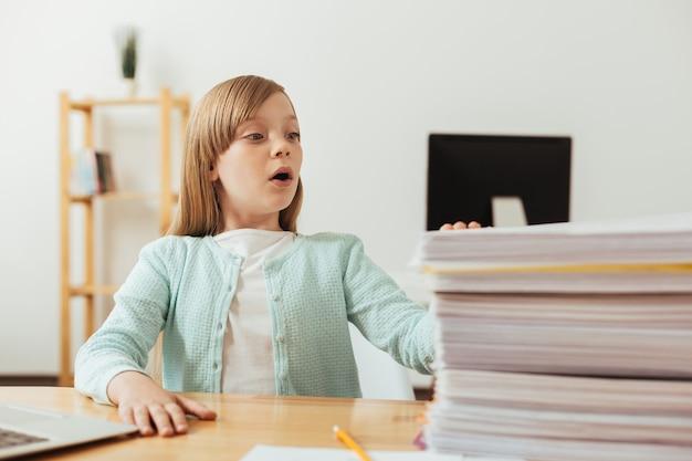Искренняя эмоциональная преданная девушка смотрит на стопку бумаг, которую ей нужно разобрать
