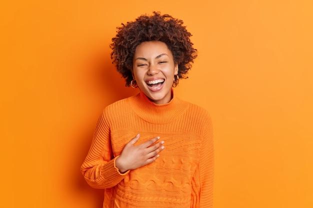 誠実な感情と前向きな感情の概念。幸せな幸せな女性の笑顔は広く胸に手を当ててオレンジ色の壁に隔離されたカジュアルなセーターに身を包んだ面白い話を笑う