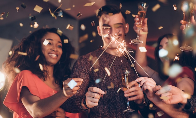 Sincere emotions. multiracial friends celebrate new year and holding bengal lights and glasses with drink