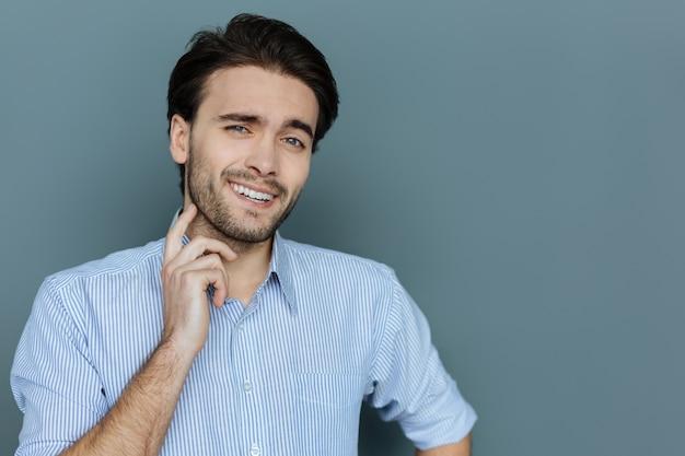 誠実な感情。彼のひげに触れながら笑顔であなたを見ているポジティブな素敵な陽気な男
