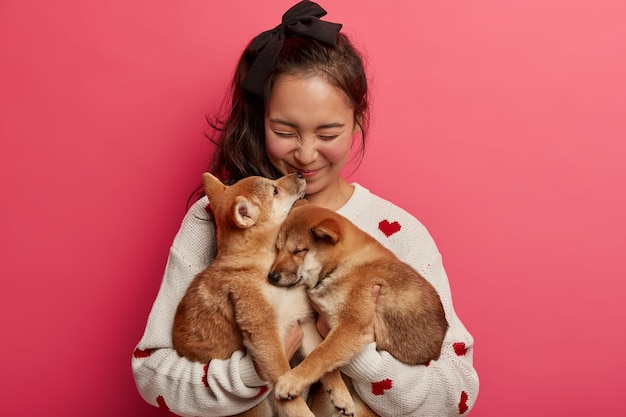 Sincere happy woman plays with two puppies, gets kiss from shiba inu dog, expresses love to animals