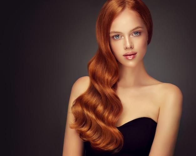 ぽっちゃりした唇に美しい青い目のバラの口紅の誠実な表情片側に集まった赤い光沢のある手入れの行き届いた長い髪の優れた波ヘアケア理髪アートとメイク