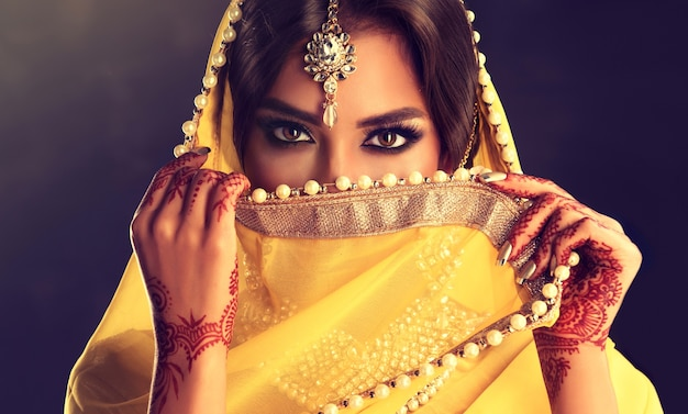 Sincere and penetrating look of beautiful black eyes above saree veil black haired indian young woman dressed in a posh yellow sari costume indian beauty